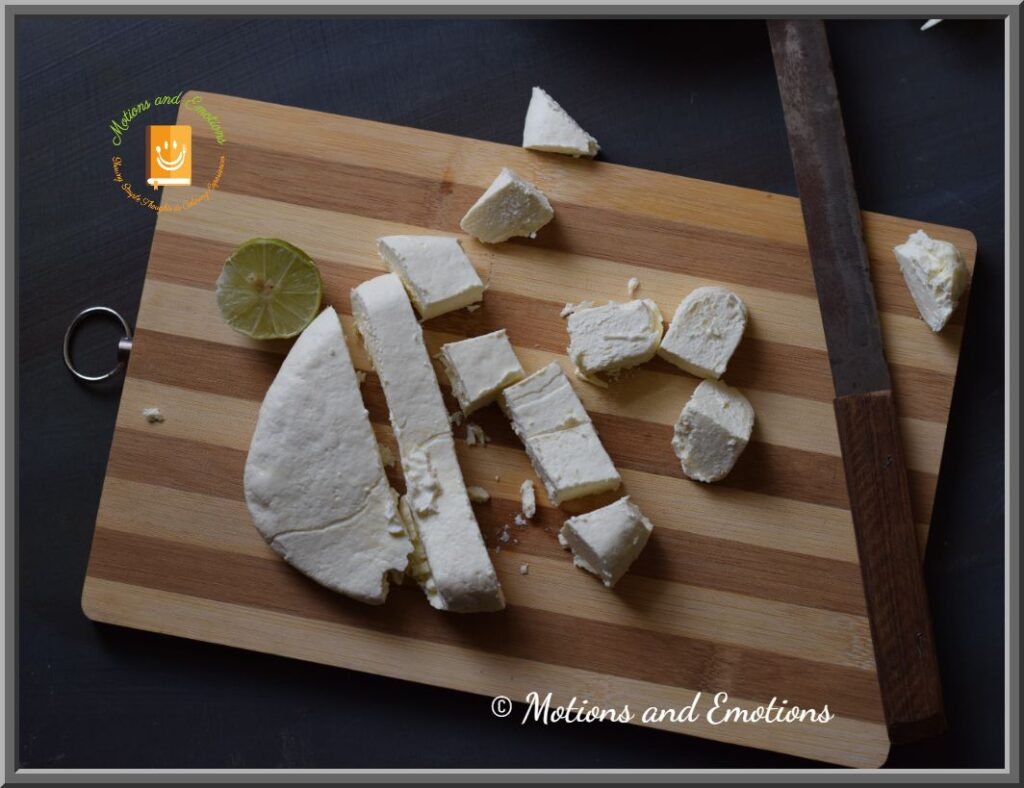 Paneer cubes cut from paneer block scattered on wooden board along with knife and lemon, top view