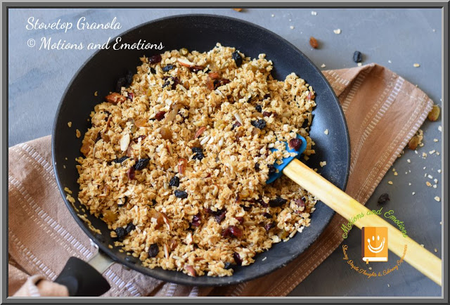Granola in a black non-stick pan along with spatula