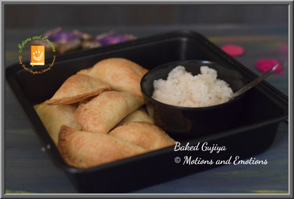 Baked Gujiya in black baking tray along with coconut stuffing in a black bowl