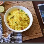 Lemon rice in a bowl along with lemon piece peanuts and kitchen towel by side top view