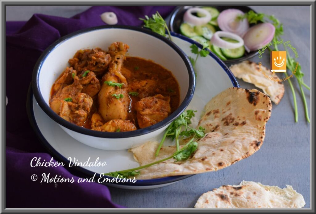 Goan Chicken vindaloo served in a white bowl on top of a white plate along with naan and salad