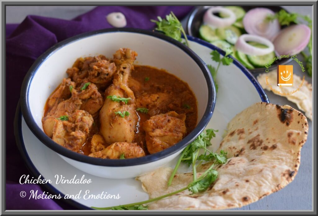 Goan Chicken vindaloo served in a white bowl along with naan and salad