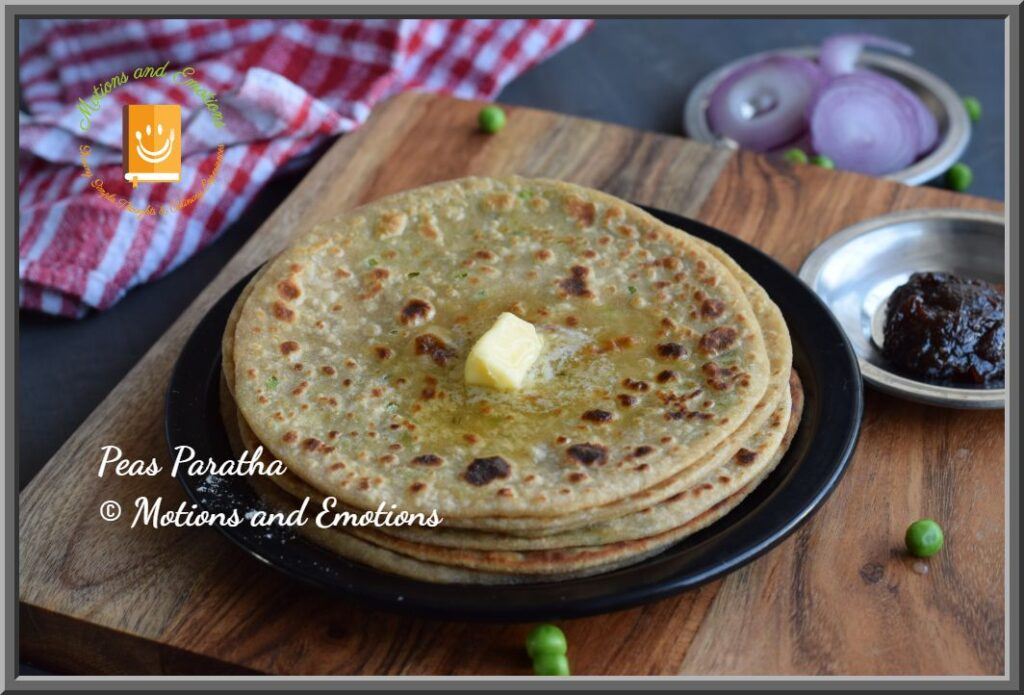 Stack of Peas Paratha with a dollop of butter served in a black plate with pickle and onion